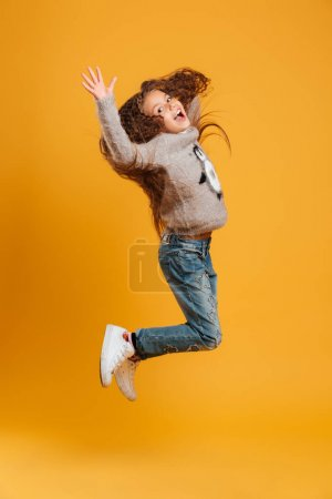 Photo for Image of excited happy little girl child jumping isolated over yellow background looking camera. - Royalty Free Image