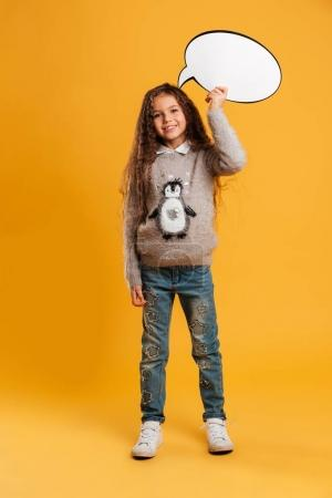 Cheerful little girl child holding speech bubble. Looking camera.