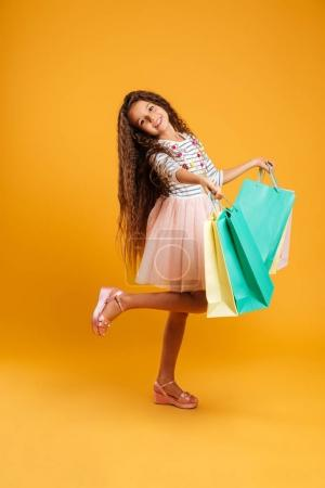 Cheerful girl child holding shopping bags.