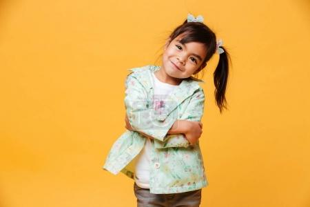 Photo for Photo of smiling little girl child standing isolated over yellow background. Looking camera. - Royalty Free Image