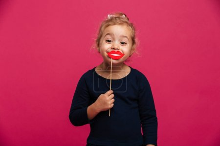 Joyful young girl using paper lips and looking at camera