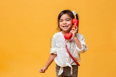 Happy excited little girl child talking by red retro telephone.
