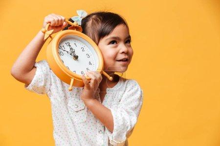 Photo pour Photo de la petite fille joyeuse enfant debout isolé sur fond jaune. Regard de côté tenant réveil alarme . - image libre de droit