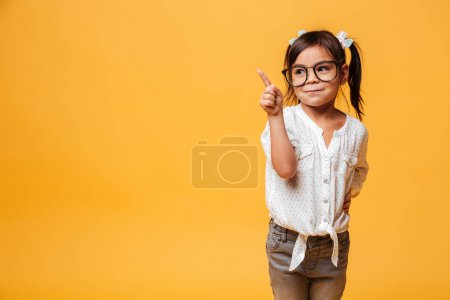 Cute little girl child wearing glasses pointing.