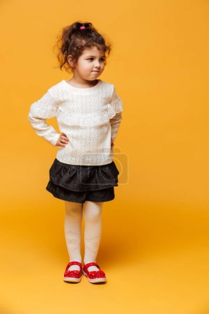 Pretty girl child standing isolated over yellow