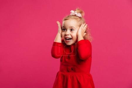 Surprised happy young girl in red dress holding her head
