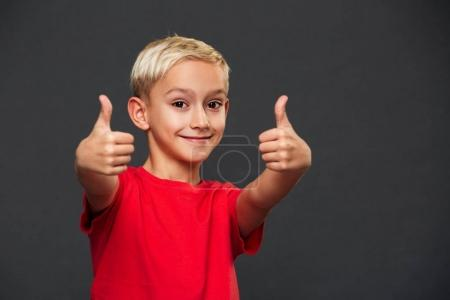 Image of smiling little boy child standing isolated over grey background. Looking camera showing thumbs up.