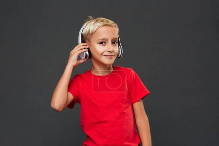 Picture of happy little boy child standing isolated over grey background. Looking camera listening music with headphones.