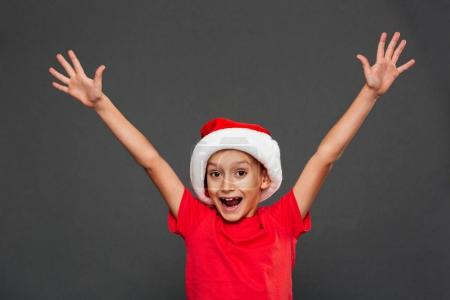 Photo of happy little boy child wearing christmas santa hat standing isolated over grey background. Looking camera.