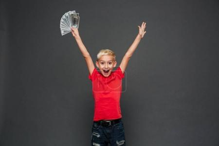 Picture of screaming surprised little boy child standing isolated over grey background. Looking camera showing money.