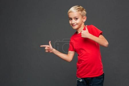 Photo of cheerful little boy child standing isolated over grey background. Looking camera pointing showing thumbs up.