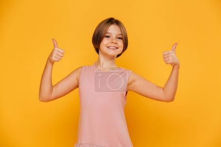 Portrait of cheerful girl smiling and showing thumbs up isolated