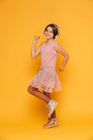 Funny smiling girl in headphones dancing isolated over yellow