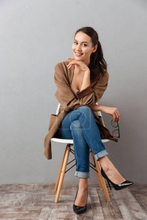 Photo for Full length portrait of a smiling casual asian woman sitting on a chair and looking at camera over gray background - Royalty Free Image