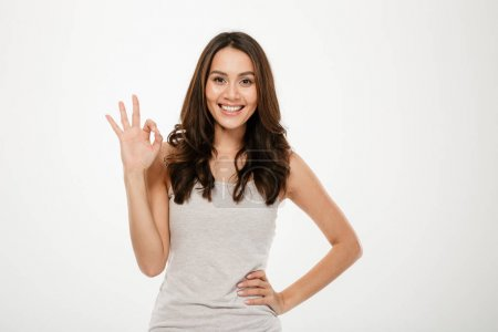 Photo pour Heureuse femme brune avec bras sur la hanche montrant ok signe et en regardant la caméra sur fond gris - image libre de droit
