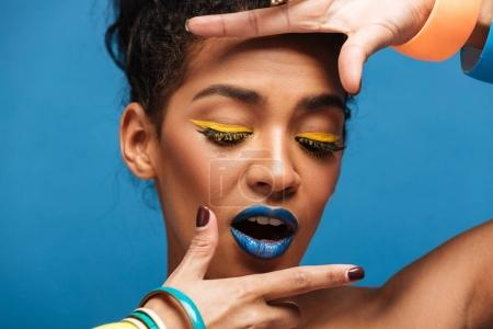 Horizontal photo of stylish mulatto woman with colorful makeup a