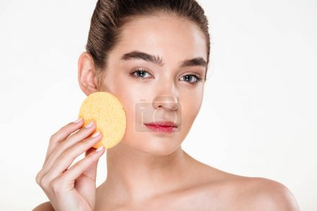 Beauty portrait of young half-naked woman using make-up sponge a