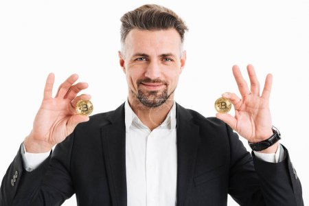Photo for Portrait of a happy mature businessman dressed in suit holding two golden bitcoins isolated over white background - Royalty Free Image