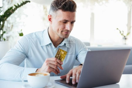 Photo pour Portrait d'un homme mûr satisfait montrant une carte de crédit dorée et utilisant un ordinateur portable tout en étant assis à la table du café à l'intérieur - image libre de droit