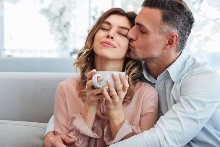 Photo of happy tender man and woman hugging and enjoying stay to