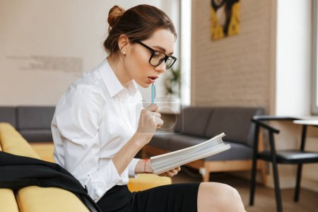 Photo for Image of young concentrated business lady writing notes in notebook sitting indoors coworking. Looking aside. - Royalty Free Image