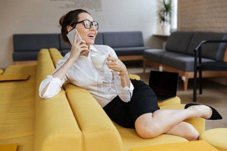 Photo pour Photo d'une jeune femme d'affaires joyeuse parlant par téléphone portable assis à l'intérieur du coworking. En regardant de côté . - image libre de droit