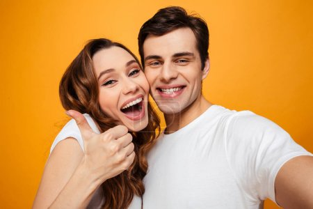 Young lovely couple posing together while making selfie and woma