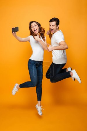 Photo for Portrait of two happy people man and woman making selfie on smartphone while jumping together, over yellow background - Royalty Free Image