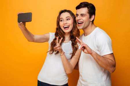 Young lovely friends smiling and making selfie on smartphone whi