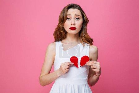 Young sad woman holding broken heart. Looking camera.