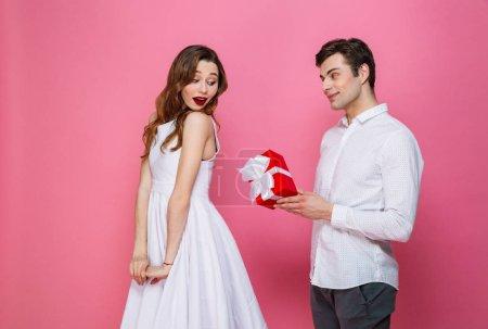 Photo pour Portrait d'un couple souriant habillé intelligemment tenant boîte cadeau isolé sur fond rose, homme donnant cadeau à sa petite amie - image libre de droit