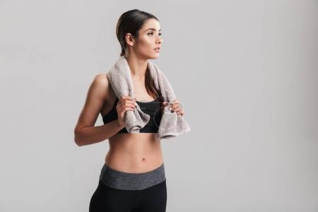 Photo of well-built fitness woman in sportswear posing with towe