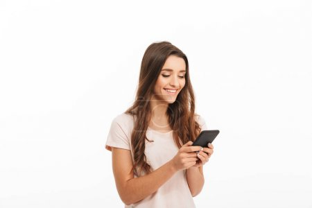 Pleased brunette woman in t-shirt writing message on smartphone