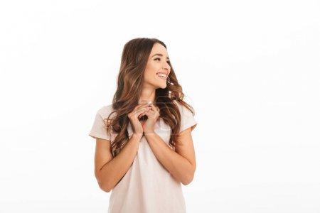 Foto de Dichoso el placer a morena mujer camiseta tomarse de las manos juntas y mirando lejos sobre fondo blanco - Imagen libre de derechos