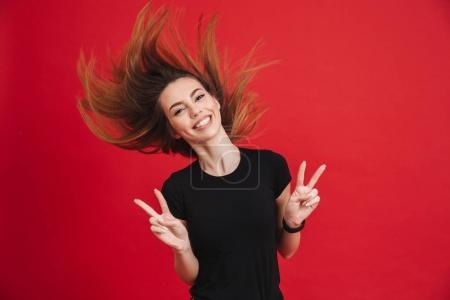 Photo pour Portrait d'une fille joyeuse, montrant le geste de paix isolé sur fond rose - image libre de droit