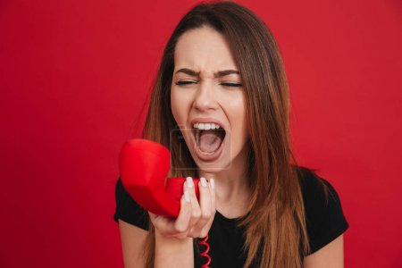 Portrait of a mad girl yelling at a landline phone