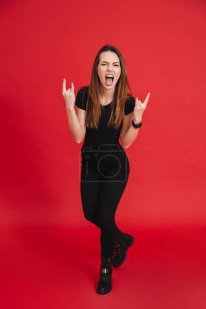 Photo pour Image pleine longueur de femme folle en tenue noire totale posant sur la caméra avec la langue sortie et des signes de roche isolés sur fond rouge - image libre de droit