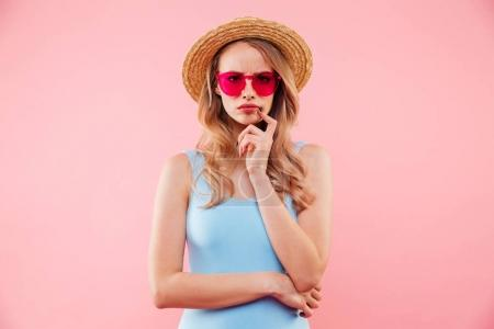 Young serious girl in sunglasses wearing colorful one-piece swim