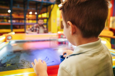 Cute little boy playing air hockey with his dad