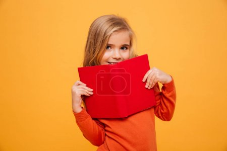Smiling young girl in sweater hiding behind the book