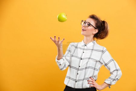 Photo for Portrait of healthy woman in plaid shirt throwing green apple up in air isolated over yellow background - Royalty Free Image