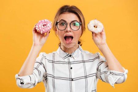 Photo pour Portrait gros plan de drôle de femme heureuse en chemise à carreaux montrant deux beignets sur la caméra isolé sur fond jaune - image libre de droit