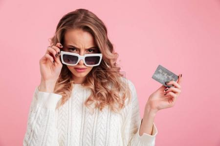 Displeased young woman holding credit card.