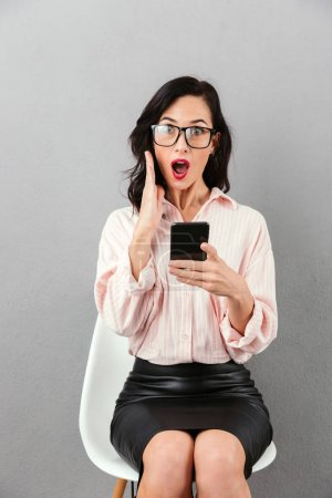 Photo for Portrait of a shocked businesswoman in eyeglasses holding mobile phone while sitting in a chair and looking at camera isolated over gray background - Royalty Free Image