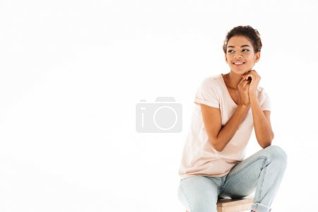 Portrait of beautiful mulatto woman sitting on chair and looking