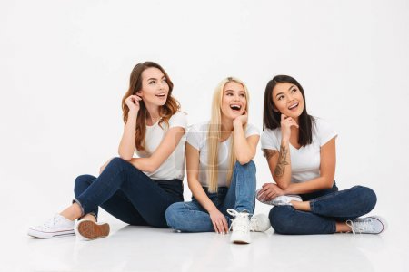 Photo for Photo of three young happy pretty girls friends sitting isolated over white background looking aside. - Royalty Free Image