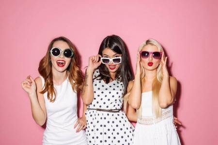 Photo pour Portrait de trois jeunes femmes gaies portant robes et lunettes de soleil en regardant caméra isolement sur fond rose - image libre de droit