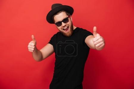 Photo pour Image d'un jeune homme excité portant des lunettes de soleil noires et un chapeau souriant et pointant du doigt sur la caméra signifiant hey vous isolé sur un mur rouge - image libre de droit