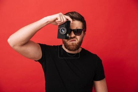 Portrait de mec musclé en vêtements décontractés et lunettes de soleil photog