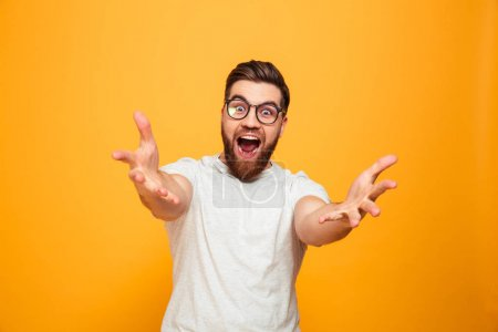 Photo for Portrait of an excited bearded man in eyeglasses standing with outstretched hands isolated over yellow background - Royalty Free Image